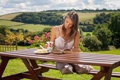 Ung attraktiv kvinna och att läsa en utomhus- bok och att tycka om kaffe Arkivfoton