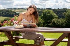 Ung attraktiv kvinna och att läsa en utomhus- bok och att tycka om kaffe Royaltyfri Fotografi