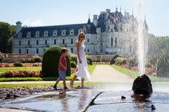 Ung attraktiv kvinna och hennes barn som förnyar med vattenspla Fotografering för Bildbyråer