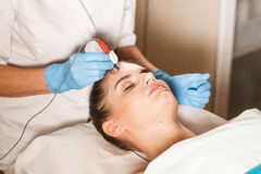 Ung attraktiv kvinna på mottagande på kontoret för kosmetolog` s Tillvägagångssättelkraftmyostimulation Maskinvarucosmetology Arkivfoton