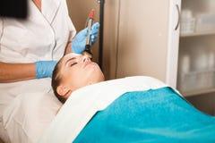 Ung attraktiv kvinna på mottagande på kontoret för kosmetolog` s Tillvägagångssättelkraftmyostimulation Maskinvarucosmetology Arkivfoto