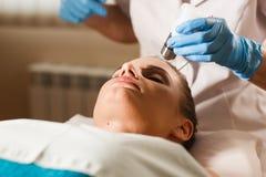 Ung attraktiv kvinna på mottagande på kontoret för kosmetolog` s Tillvägagångssättelkraftmyostimulation Maskinvarucosmetology Fotografering för Bildbyråer