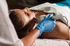 Ung attraktiv kvinna på mottagande på kontoret för kosmetolog` s Tillvägagångssättelkraftmyostimulation Maskinvarucosmetology Royaltyfri Bild