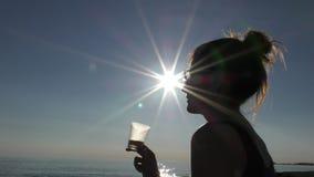 Ung attraktiv kvinna på stranden på solnedgången som dricker från exponeringsglas arkivfilmer