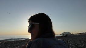 Ung attraktiv kvinna på stranden på solnedgångtid arkivfilmer