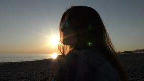 Ung attraktiv kvinna på stranden på solnedgångtid stock video