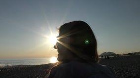 Ung attraktiv kvinna på stranden på solnedgångtid som talar om något stock video