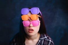 Ung attraktiv kvinna som bär många vibrerande retro solglasögon Fa Royaltyfria Foton