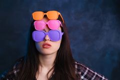 Ung attraktiv kvinna som bär många vibrerande retro solglasögon Fa Arkivfoto