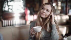 Ung attraktiv kvinna som dricker kaffe eller te i kafét, steadicamskott arkivfilmer