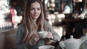Ung attraktiv kvinna som dricker kaffe eller te i kafét, steadicamskott lager videofilmer
