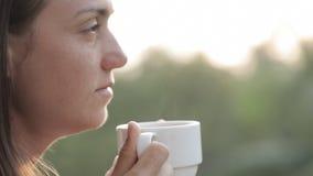 Ung attraktiv kvinna som dricker kaffe eller te på balkongen, närbild arkivfilmer