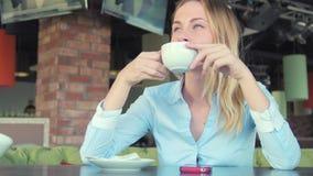Ung attraktiv kvinna som dricker kaffe i kafé arkivfilmer