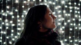 Ung attraktiv kvinna som framme tycker om fallande snö på julnatten av den dekorativa väggen mycket av mousserande ljus lager videofilmer