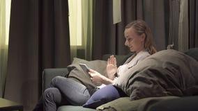 Ung attraktiv kvinna som har video pratstund över internetwifi Härligt kvinnligt samtal till föräldrar som delar nyheterna med arkivfilmer
