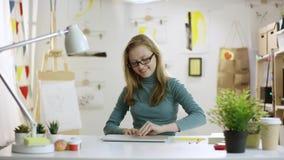 Ung attraktiv kvinna som kastar böcker ut ur tabellen och öppnar bärbara datorn till att surfa internet stock video