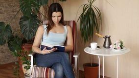 Ung attraktiv kvinna som läser den intressanta boken, medan sitta på bekväm stol i vardagsrummet lager videofilmer