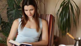 Ung attraktiv kvinna som läser den intressanta boken, medan sitta på bekväm stol i vardagsrummet close upp lager videofilmer