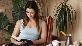 Ung attraktiv kvinna som läser den intressanta boken, medan sitta på bekväm stol i vardagsrummet close upp arkivfilmer