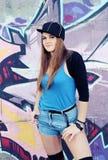 Ung attraktiv kvinna som poserar mot grafitti Royaltyfria Foton
