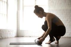Ung attraktiv kvinna som rullar ut matt yoga, vit vindstudiobac fotografering för bildbyråer
