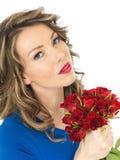 Ung attraktiv kvinna som rymmer en grupp av röda rosor Royaltyfria Bilder