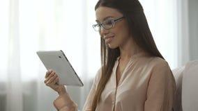 Ung attraktiv kvinna som ser in i kamera med en minnestavla, tillfredsställd person stock video