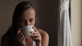 Ung attraktiv kvinna som ser till fönstret och dricker te lager videofilmer