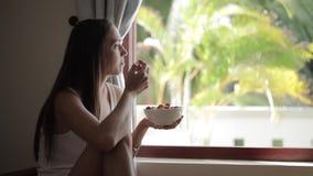 Ung attraktiv kvinna som sitter nära fönster och äter körsbärsröda tomater från bunken stock video