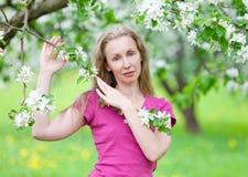 Apple-tree trädgård i fjädra under en säsong av blomning- och barnженжина blondinen bland trees Arkivbild