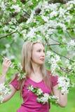 Apple-tree trädgård i fjädra under en säsong av blomning- och barnkvinnan blondinen bland trees Royaltyfri Bild