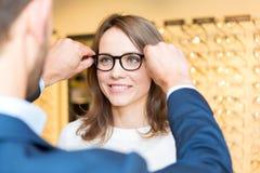 Ung attraktiv kvinna som testar nya exponeringsglas med optiker Royaltyfri Bild