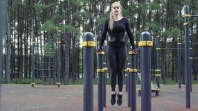 Ung attraktiv kvinna som utomhus gör övningar för buk- muskel arkivfilmer