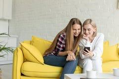 Ung attraktiv kvinna tv? i tillf?llig kl?der som hemma sitter p? den gula soffan arkivbilder