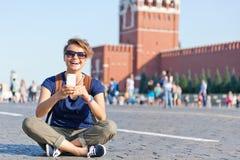 Ung attraktiv kvinnahandelsresande med ryggsäck- och mobiltelefonnolla Royaltyfria Bilder