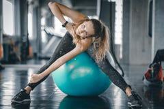 Ung attraktiv kvinnakondition som gör övningsgenomkörare i idrottshall Kvinna som sträcker musklerna och koppla av arkivfoto