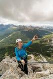 Ung attraktiv kvinnlig bergsbestigare på ett brant och utsatt via Ferrata i Alta Badia i den södra Tyrolen i den italienska Dolom royaltyfri fotografi