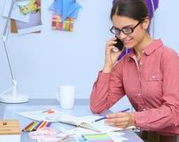 Ung attraktiv kvinnligmodeformgivare som fungerar på kontorsskrivbordet som tecknar, medan tala på mobil arkivbilder