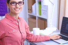 Ung attraktiv kvinnligmodeformgivare som fungerar på kontorsskrivbordet som tecknar, medan tala på mobil royaltyfria bilder