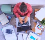 Ung attraktiv kvinnligmodeformgivare som fungerar på kontorsskrivbordet som tecknar, medan tala på mobil arkivfoto