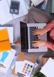 Ung attraktiv kvinnligmodeformgivare som fungerar på kontorsskrivbordet som tecknar, medan tala på mobil arkivbild