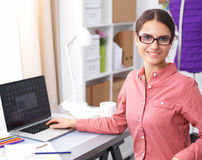 Ung attraktiv kvinnligmodeformgivare som fungerar på kontorsskrivbordet som tecknar, medan tala på mobil fotografering för bildbyråer