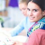 Ung attraktiv kvinnligmodeformgivare som fungerar på kontorsskrivbordet som tecknar, medan tala på mobil royaltyfria foton
