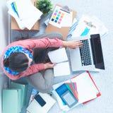 Ung attraktiv kvinnligmodeformgivare som fungerar på kontorsskrivbordet som tecknar, medan tala på mobil royaltyfri bild