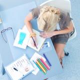 Ung attraktiv kvinnligmodeformgivare som fungerar på kontorsskrivbordet som tecknar, medan tala på mobil royaltyfri foto