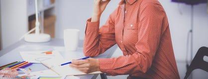 Ung attraktiv kvinnligmodeformgivare som fungerar på kontorsskrivbordet som tecknar, medan tala på mobil arkivfoton