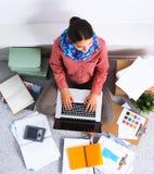 Ung attraktiv kvinnligmodeformgivare som fungerar på kontorsskrivbordet som tecknar, medan tala på mobil royaltyfri fotografi