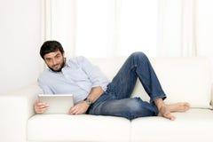 Ung attraktiv latinamerikansk man hemma på den vita soffan genom att använda den digitala minnestavlan eller blocket Arkivbilder