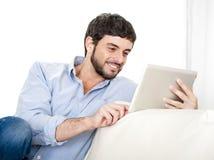 Ung attraktiv latinamerikansk man hemma på den vita soffan genom att använda den digitala minnestavlan eller blocket Royaltyfri Bild