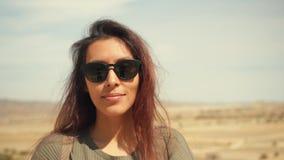 Ung attraktiv le blandad sprungen flickastående i en öken Lycklig turist- kvinna som poserar på kamera med hår som vinkar i vinde arkivfilmer